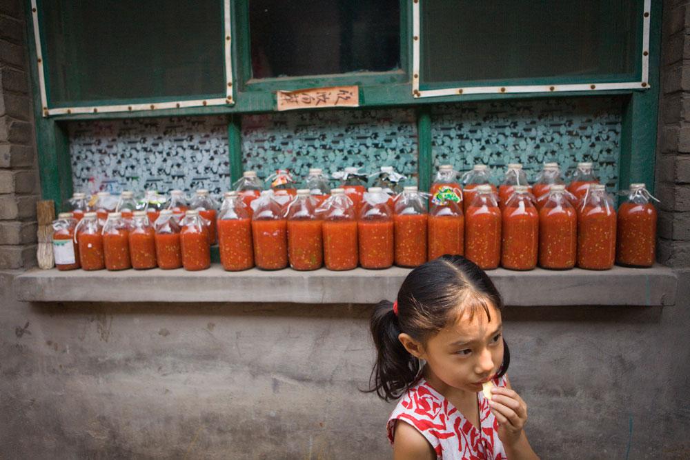 A young girl plays outside while tomatoes roast in the sun in Pingyao, China. Richard U. Light Foundation.