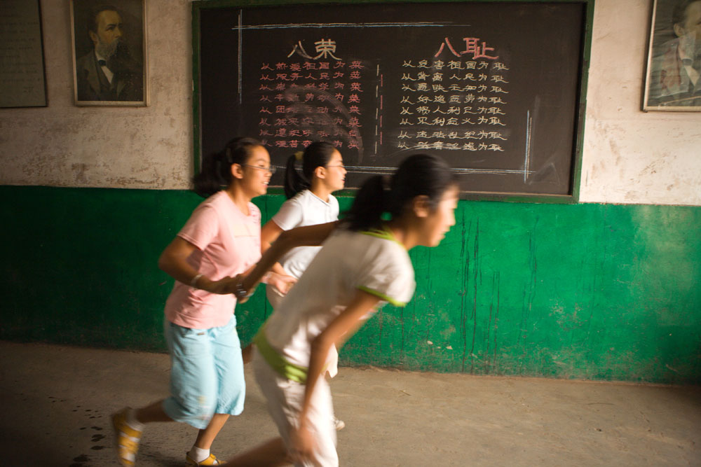 3 friends run out the front door of their school for recess while attending summer school in Pingyao, China.Richard U. Light Foundation.