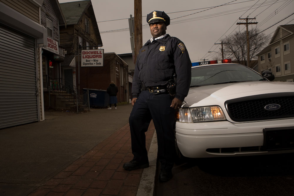 New Haven police officer and graduate of Yale University, Anthony Duff, stands on the street he regulary patrols. Yale Alumni Magazine.