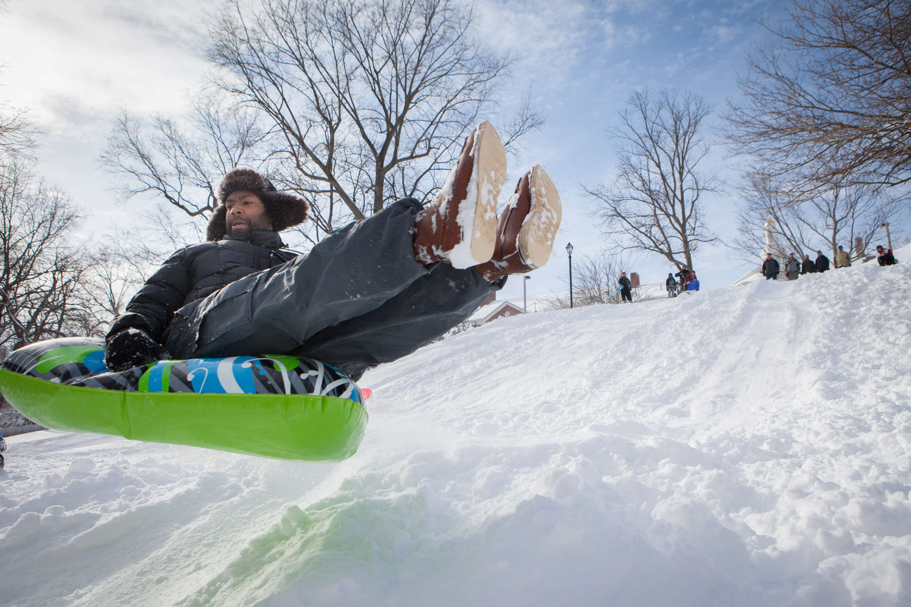 A member of the Yale University community takes a break from his daily routine to sled down a hill on the snowiest day of the winter. Yale Alumni Magazine
