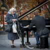 A woman listens to Colin Huggins play the piano in Washington Square Park in Greenwich Village, NY.