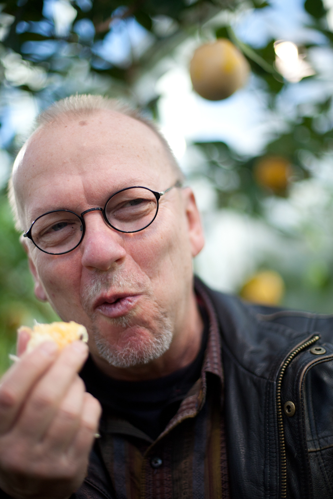 Eric Larson, manager of the Marsh Botanical Gardens eats an orange picked from a tree grown in one of the greenhouses.
