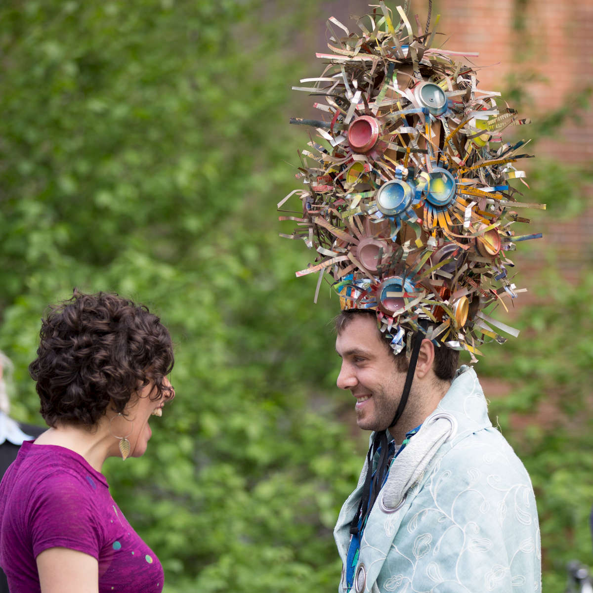 A participant in the 6th annual Mudball Ball talks with a friend at el jardinde paradiso on 4th st between Ave's C and D . The Winter Flower Crown is made of previously used cans by trash worship artist Rolando Politi aka Kappo Kappino. The 6th Mudball Ball is a garden celebration of bioremediation.
