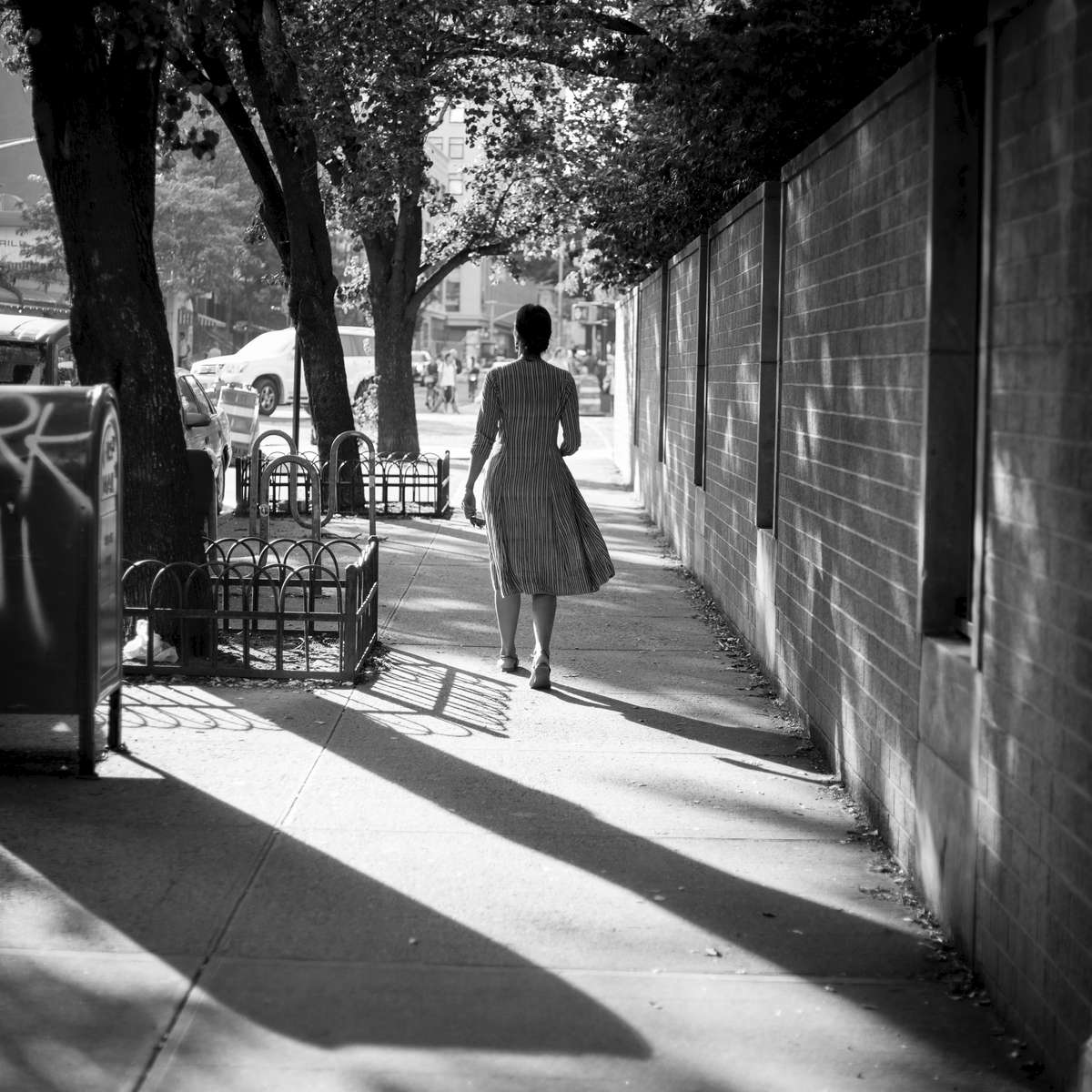 A woman walks west on 4th street on a hot summer day.