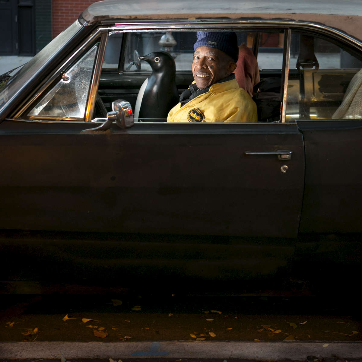 Photographer Alex Harsley sits in his 1968 Dodge dart with his plastic penguin {quote}the navigator{quote} outside The 4th street Photo Gallery which he owns and has run since its opening in 1973. Harsley, who is in his 70's has seen and photographed a ton of new york history including a few years working for the district attorney's office until he was drafted in 1961. These days Harsley shoots with his phone rather than the large format camera he used to use. More of his work can be seen here: http://www.fith-artcollective.jimdo.com/.