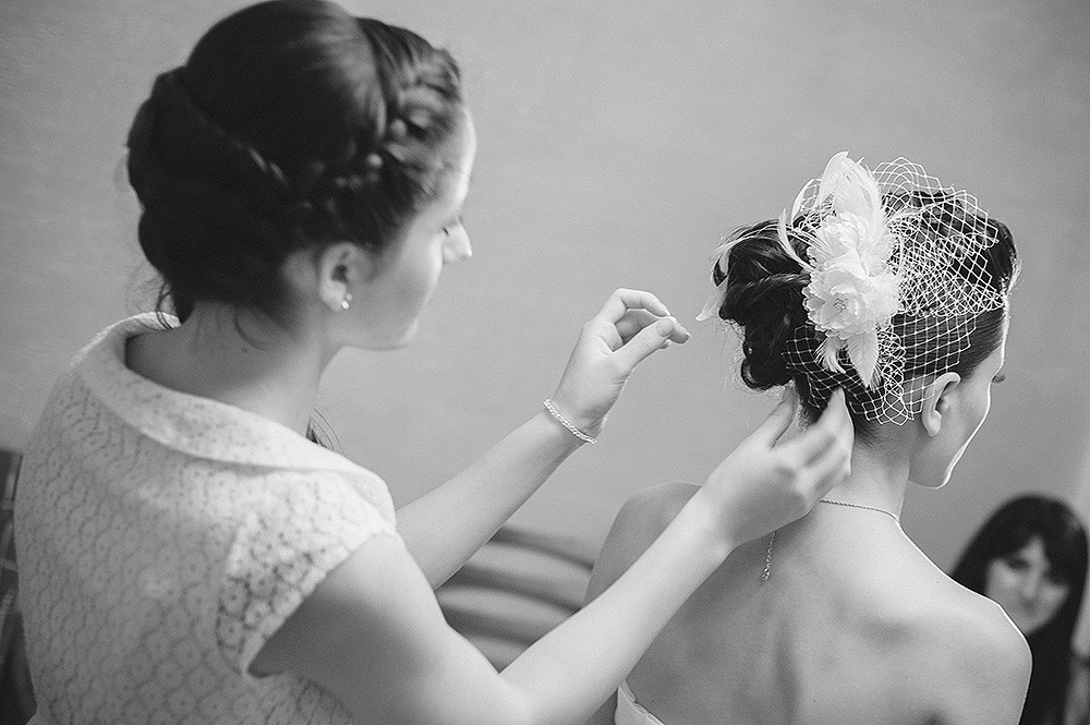 Daniela, a young beautiful bride hair's being arranged by professional hair stylist