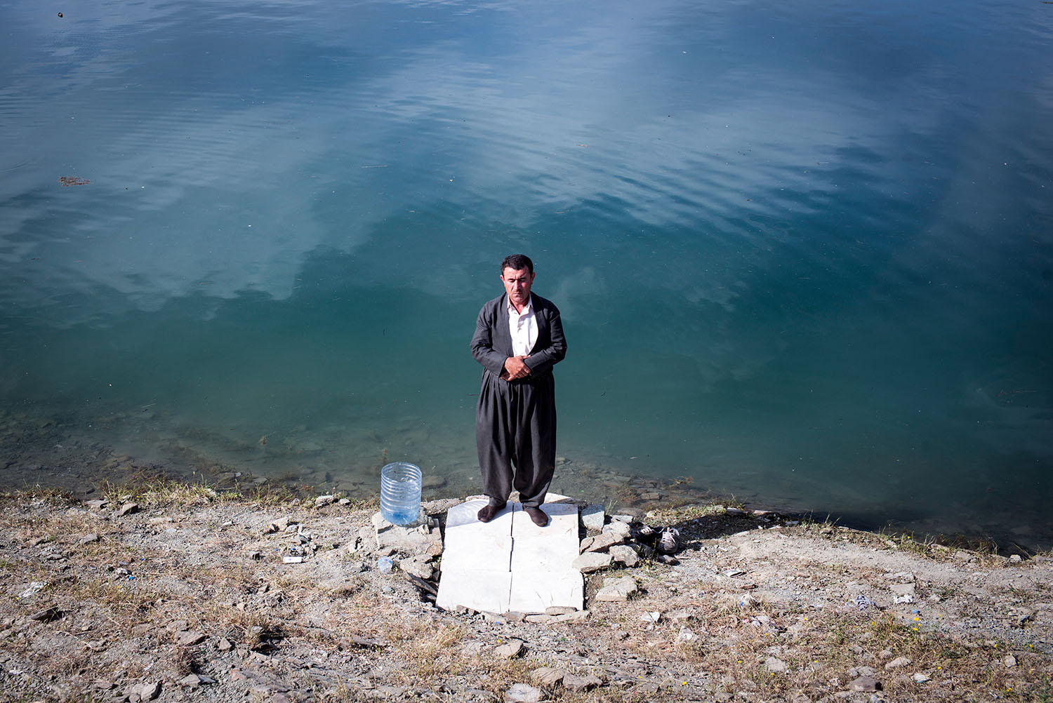 A man prays by the shore of the Dukan Lake in Suleymaniyah.