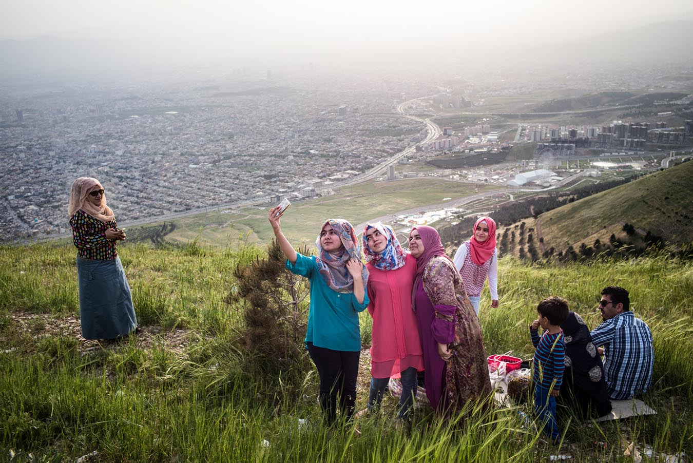 A family take selfie photo with view of Suleymaniyah from Azmar Mountain.