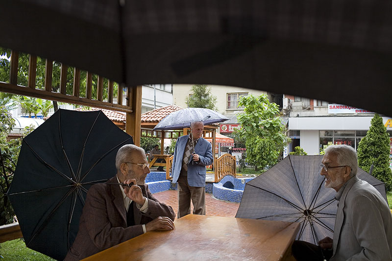 Elderly locals sit in a park during the rain at Cayeli.