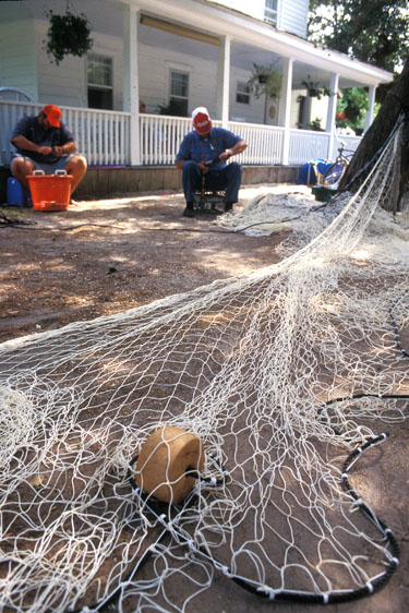 fishermen mend their nets beside their home in Ocracoke North Carolina