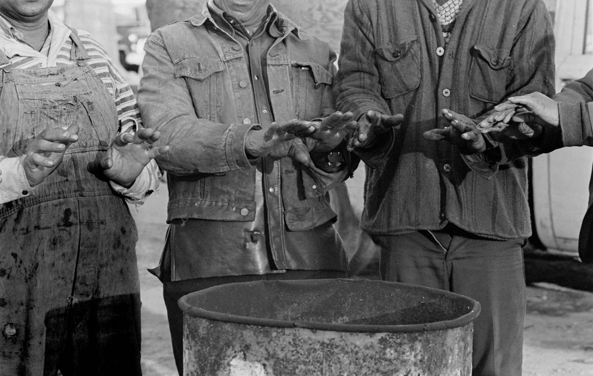 January, 1994 - Some men take a break from clearing a trash strewn lot to warm their hands In the middle of winter on Manhattan Avenue in Harlem,