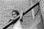 A child looks at the activity in the alley from the backstairs of the tenement where she lives.