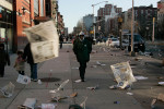 March 2006 - High winds blow loose newspaper pages around 125th near the IRT Subway entrance as some people make their way to work that morning.
