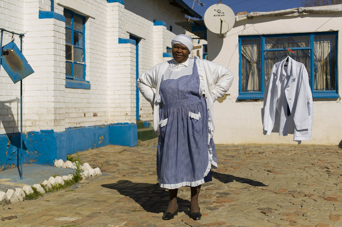 Ntsoaki Pila, 37, in the church yard of St. John Apostolic Faith Mission Church. The service hadn't started, and she stopped washing church garments in a shed in the back to pose for this picture.
