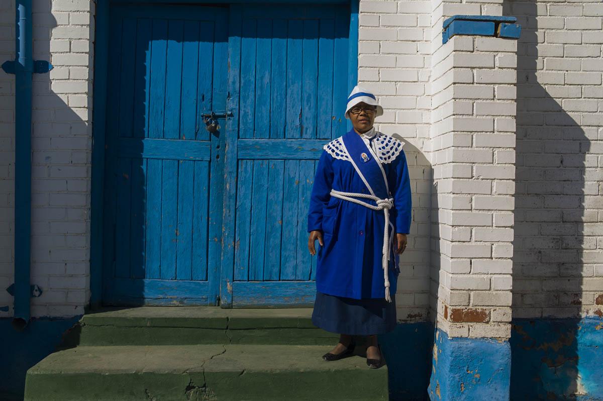 Mitta Mabena, 54, poses in her Sunday worship dress at the door of St. John Apostolic Faith Mission Church.