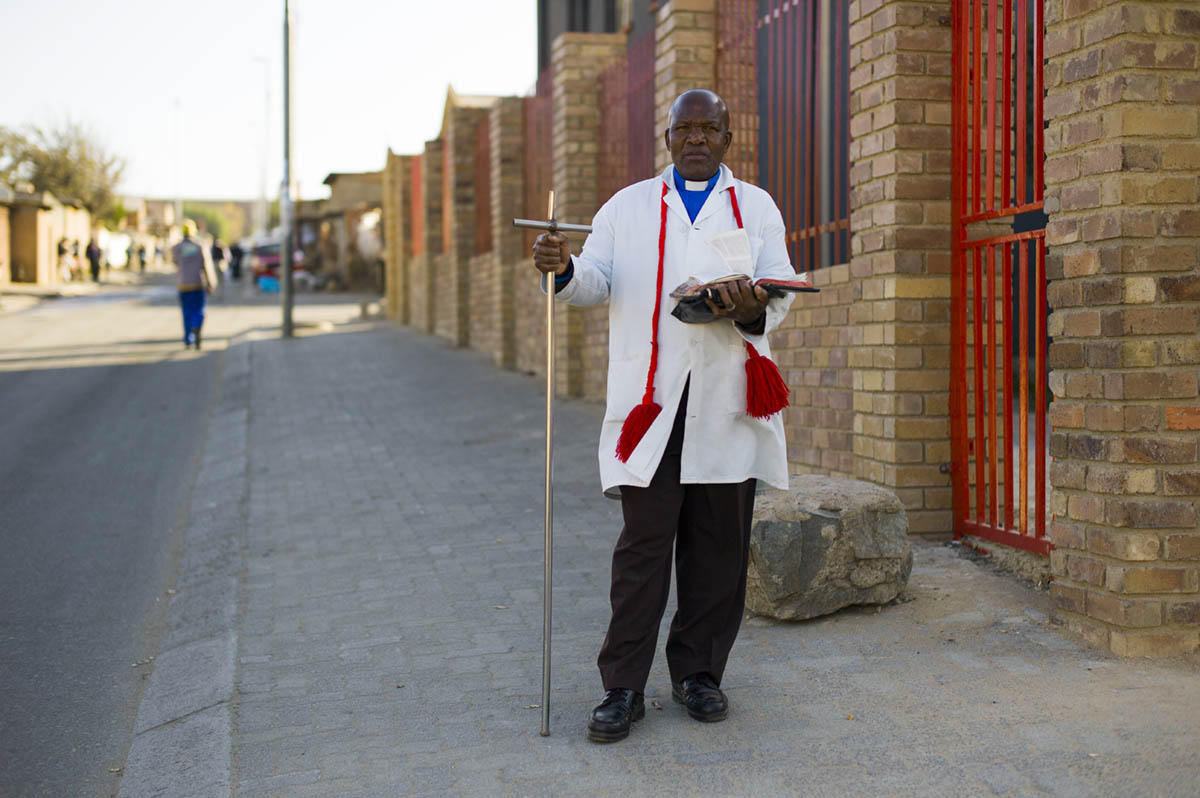Rev. Frans Kgolane, 61, who leads a congregation at The Baptist Apostolic Church. He was on his way home after service. The long cross is very common among the men, whether they are the ministers or simply a part of the congregation. The staff conveys that Jesus was a shepherd.