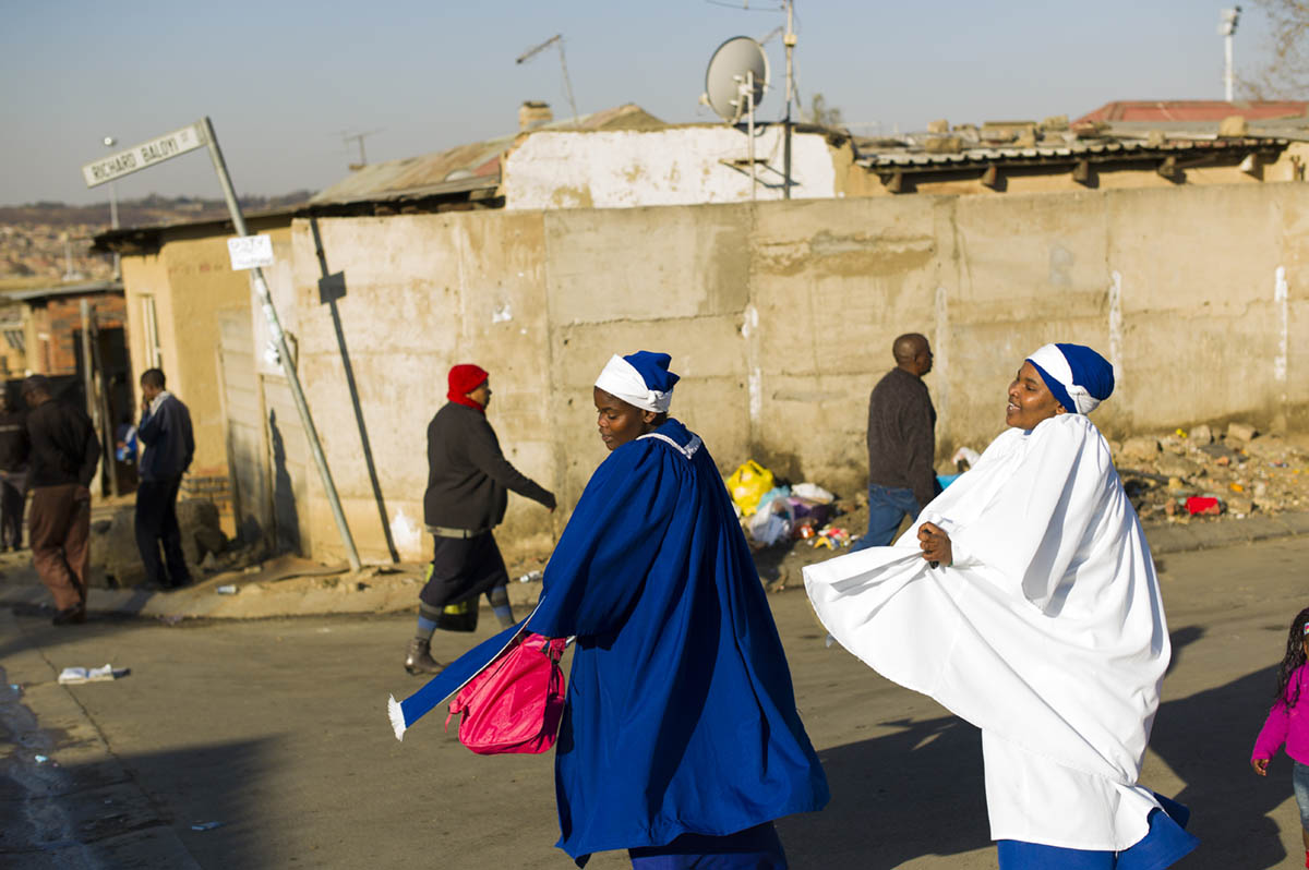 The woman in white was so carried away in moments of what appeared to be ecstasy, from a sermon she had just heard, danced in the street on her home with her friend Sinazo Makunge, in Alexandra Township (as they headed home the photographer tried to get her name and few words from her to no avail, she was in a moment that she would not let go). Ms. Makunge, was able to engage others: not so with the woman in white.