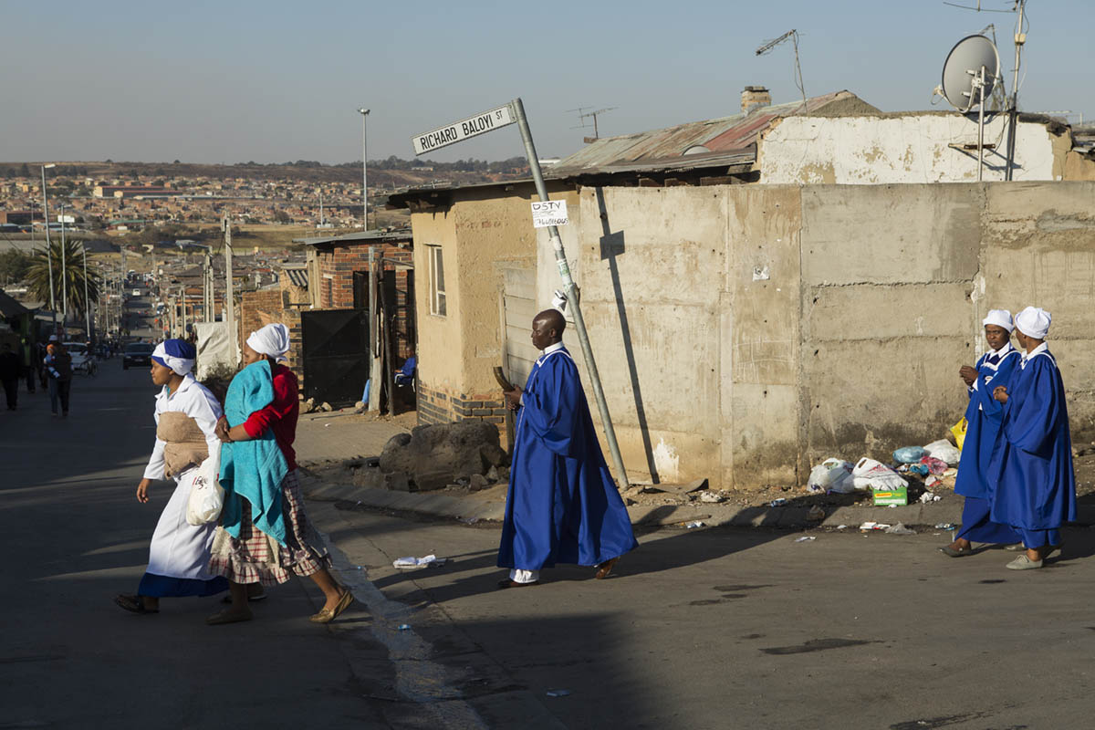 A group of worshippers head home (most church services are over at this time - it was near dusk and there is a little to no electricity in Alexandra Township) from a service. Their garments indicate the congregation or christian association they are a part of. The man in the middle is holding a very beautifully carved staff. The kind one would see in common biblical illustrations.