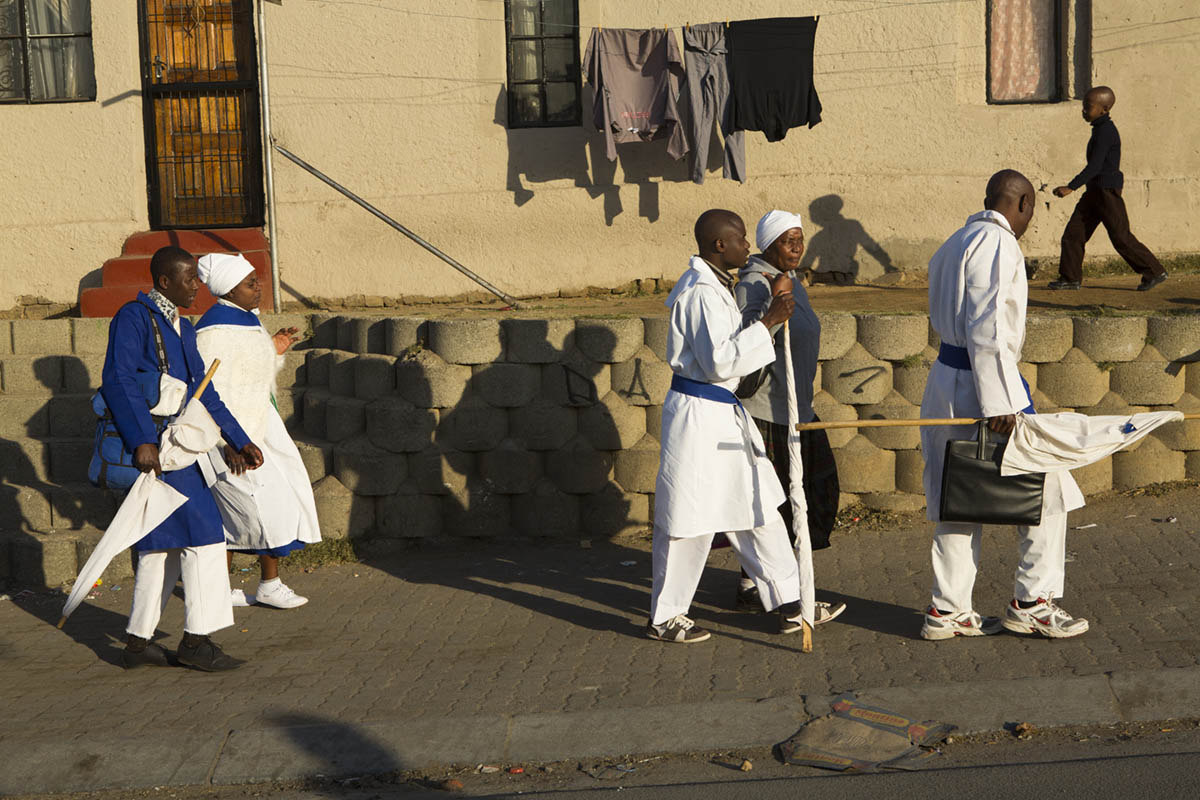 Church goers heading home after service. The men often are seen with staffs and banners. The idea of the dress, especially with the men is to depict the worshippers as shepherds, like Jesus Christ.