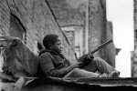 This boy was perched on the roof of a garage behind a tenement building in the Bronzeville neighborhood, holding a toy rifle.