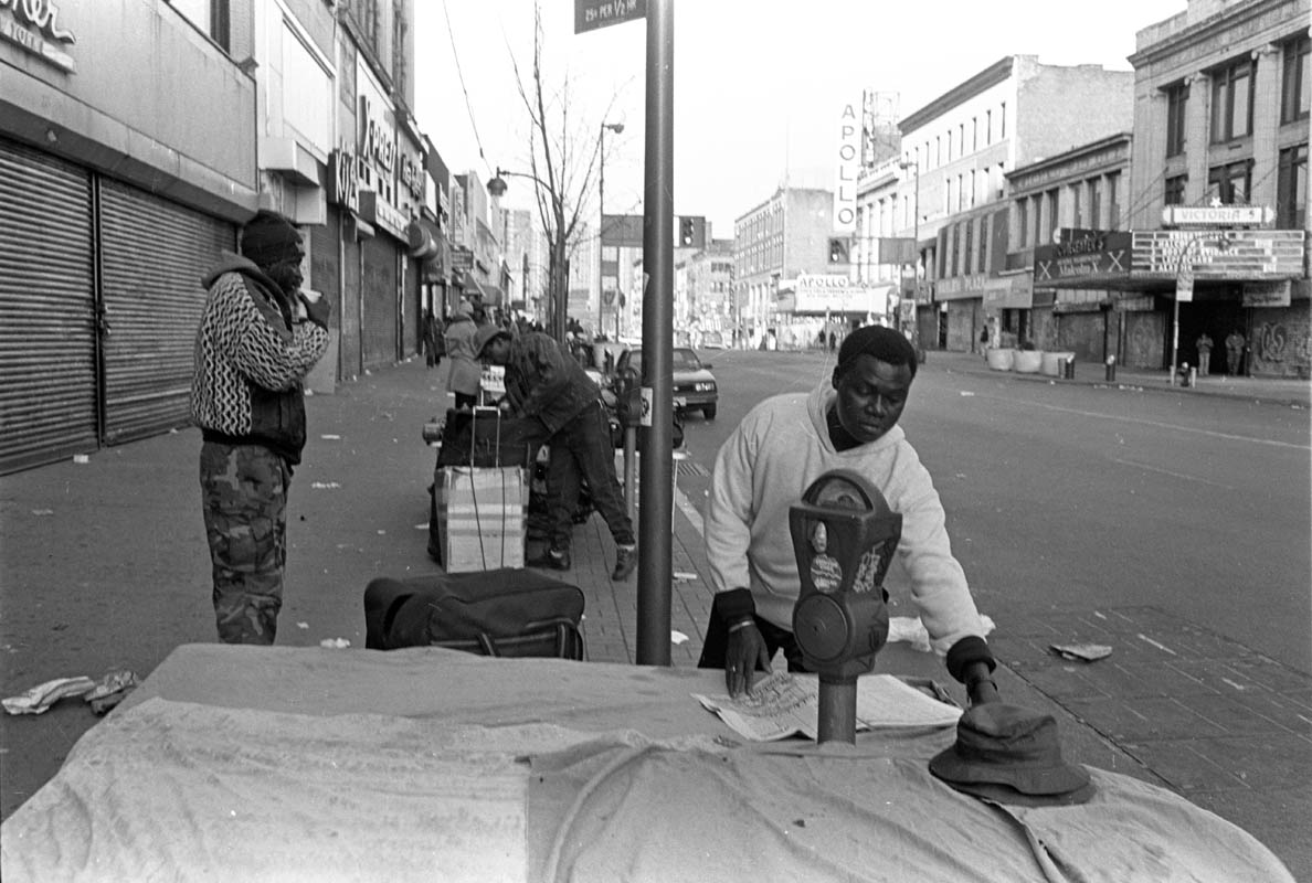 June, 1993 - A street vendor prepares his merchandise on an early Sunday morning near the Apollo Theater in Harlem.