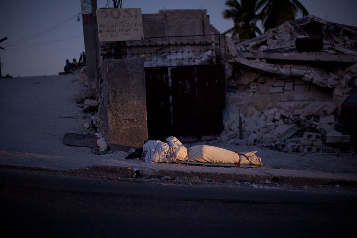 01-21-10  - POUPELARD STREET -  A corpse was pulled from the rubble in a building in the background here on Poupelard. It was put here on the sidewalk under an SOS sign, with the hope that an agency of the Haitian government will pick it up and see that it is properly buried. - Ozier Muhammad/The New York Times