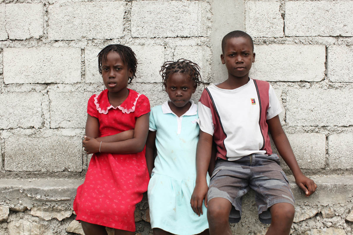 01-26-10 Croix Des Bouquets, Haiti - Orphans of the January 12th earthquake are gathered in a field next to Lycee Jacques, a primary school. They are under the care of FRADES, a grass organization which is providing foster care. Portrait of orphans; Anite (accent aigue over the {quote}E{quote}), 9, Rosemita, 6 and Jhonny, 12. They are siblings and their last name is Charles.Two sisters and their brother: Anite, nine, Rosemita, six and Jhonny Charles, 12. - Ozier Muhammad/The New York Times