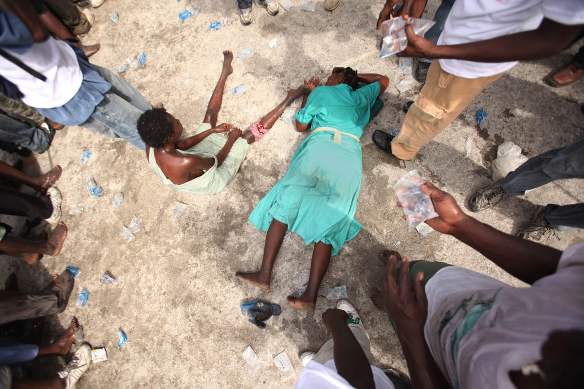 Cite Soleil, Haiti - Deskl: FOR - Slug: - PREVAL-FOOD - These 2 women collapsed while struggling to reach the entrance to this police headquarters where the government of Rene Preval handed out 10,000 bags of food, worth $50 each.  Six thousand of those food bags were provided for those who could bear the crush of the crowd and the high temperature. - Ozier Muhammad/The New York Times