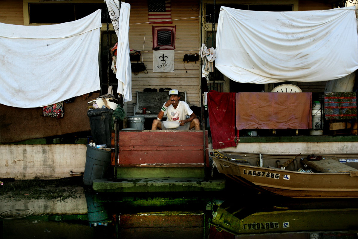 New Orleans - Late August 2005 - A sits on the the front porch of his home in the lower 9th ward surrounded by water from the breahced 17th Canal, after huuricane Katrina swept through this region. Photo by Ozier Muhammad/NYT