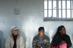 Visitors on the tour listen to a guide describe what it was like to be a political prisoner here.