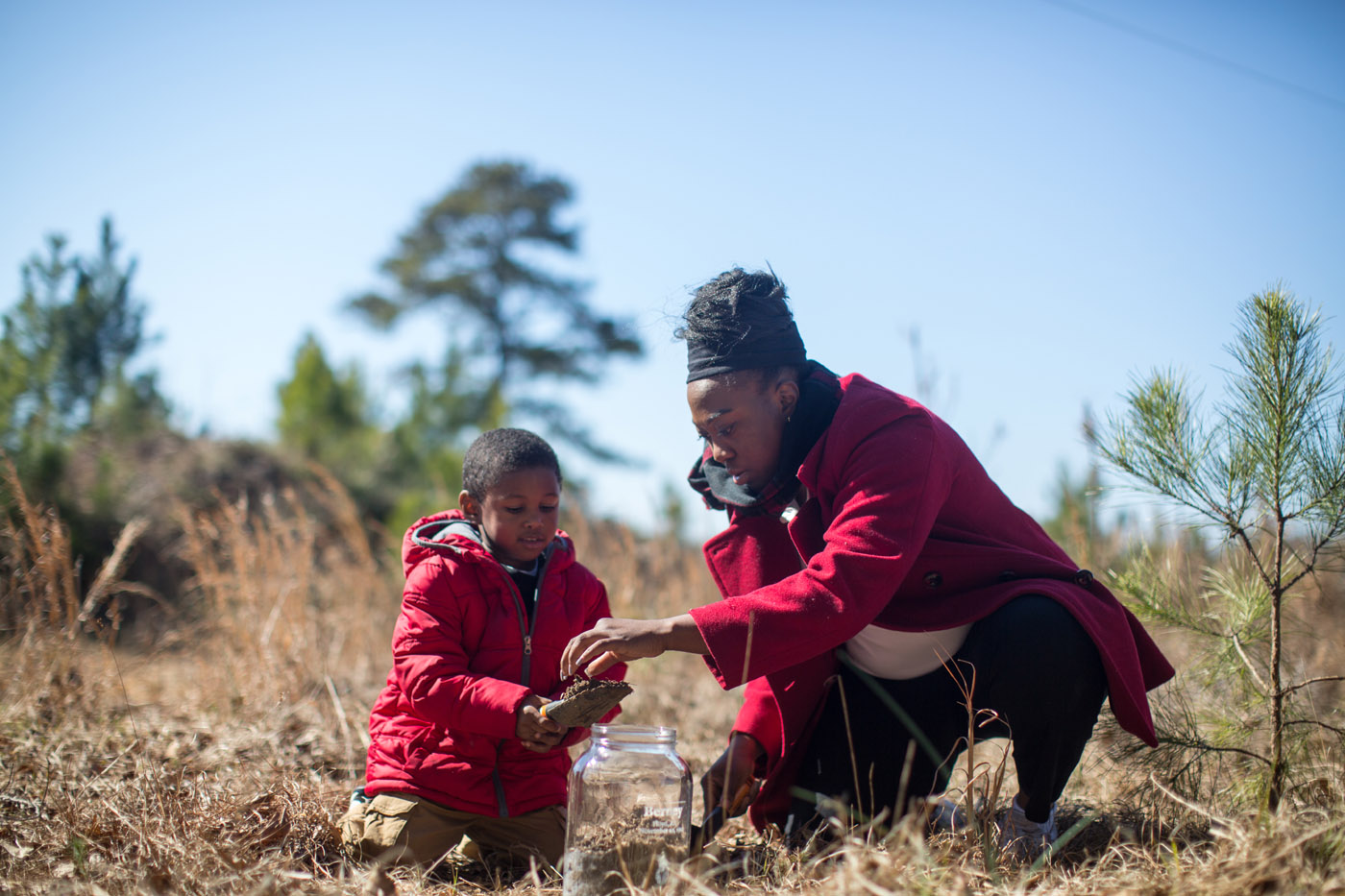Floyd, Ala - 02-12-16 - Julia Ware, 25, collects soil at the sight where a black man named Berney was lynched, on Nov 10, 1912. Her nephew, Jai Lee, 3, tagged along. She was one of many volunteers who colleced soil collecting for the lynch site project for the Equal Justice Initiative. - Credit Photo by Ozier Muhammad
