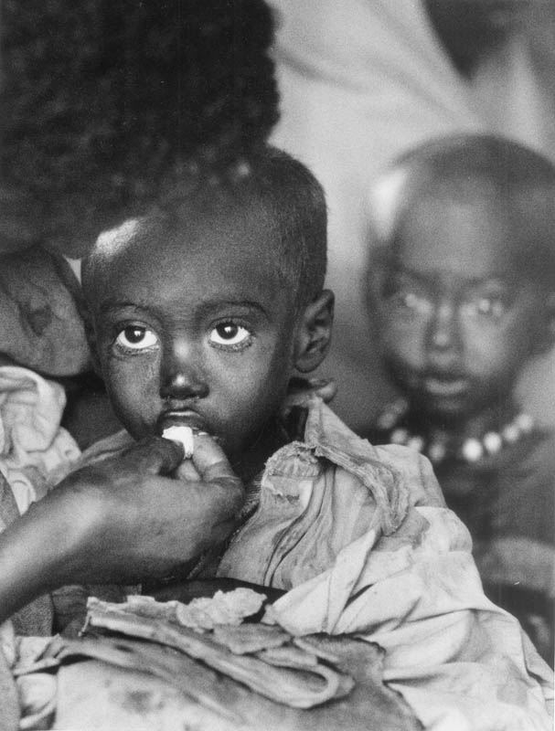 Children as they were being fed by the surviving parent, or parents in a dislocation camp.