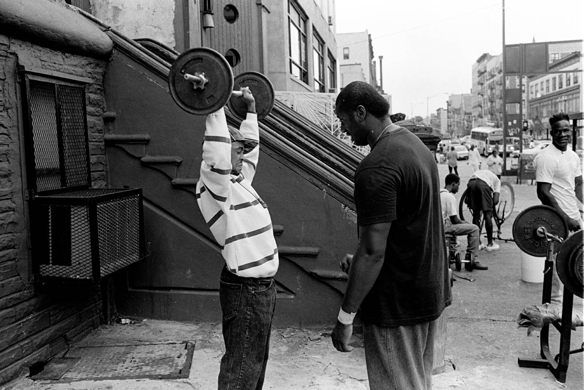May, 1994 - A man lifts weights and gets a shout of encouragement at 125th street and 5th avenue.