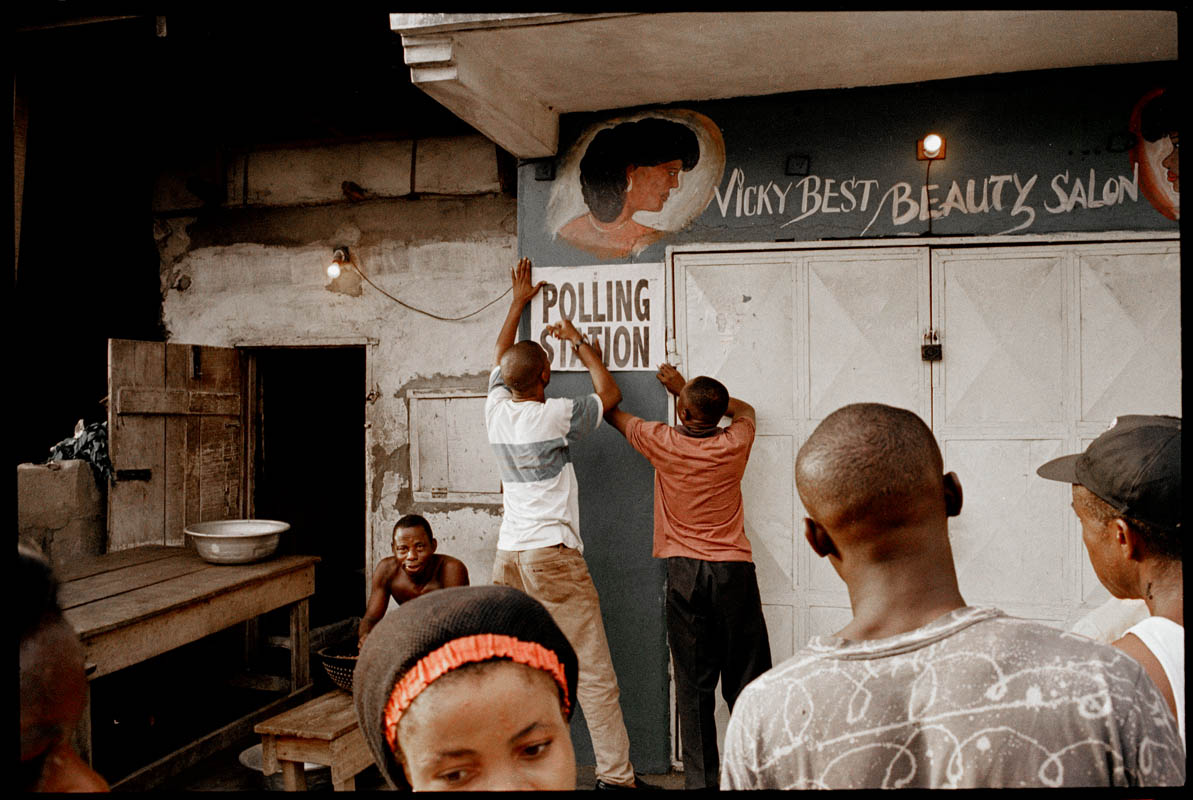 These men are hanging a sign for voters to be informed that a polling place is here. A few days later Nigeria held it's first democratic election.