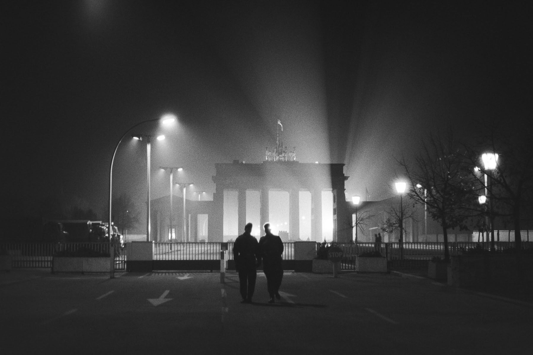 East German soldiers lit by the lights of the western world through the Brandenburg Gate on November 10, 1989