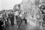 A West Berliner hitting the wall next to the Brandenburg Gate on November 10, 1989