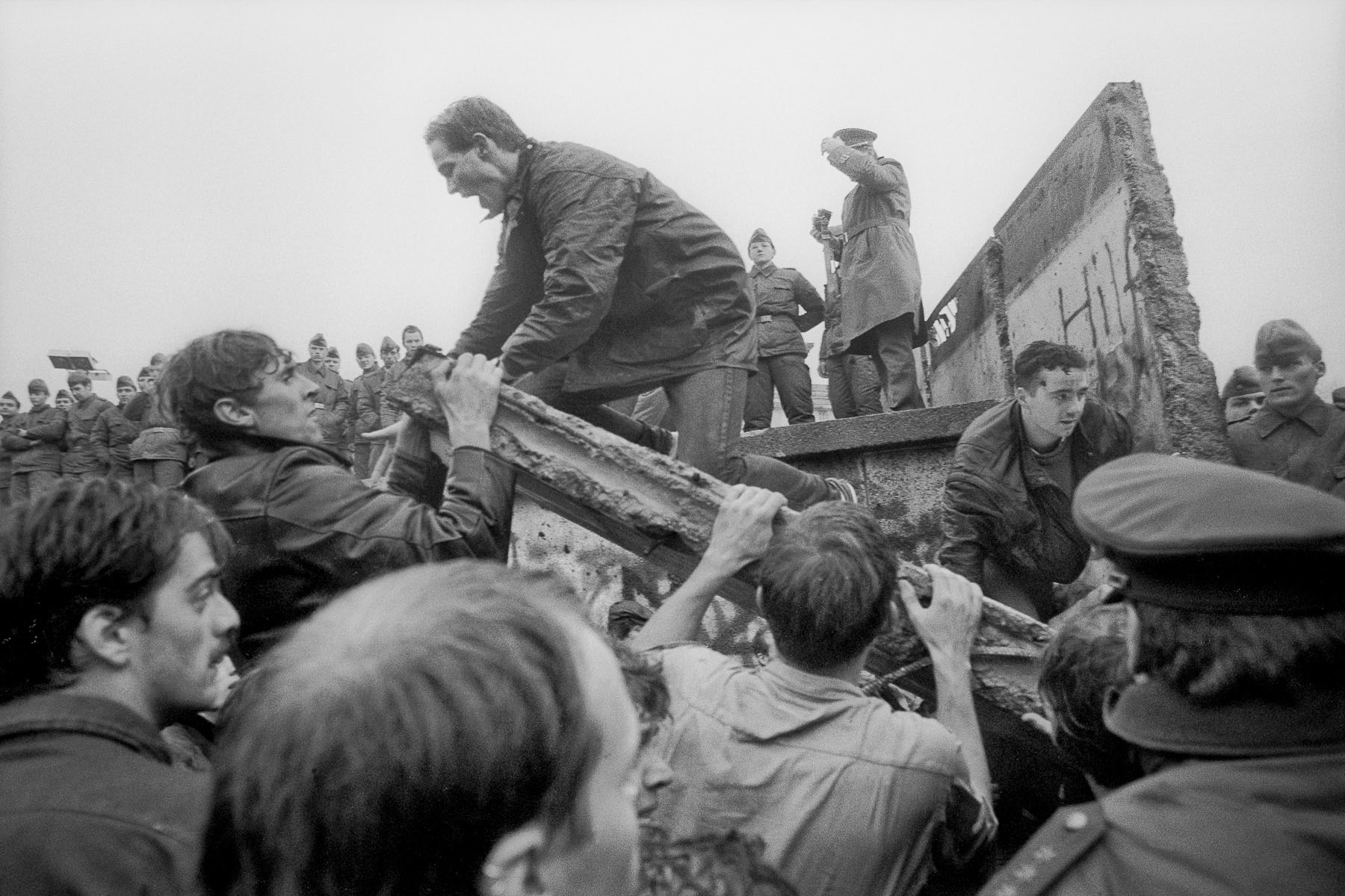West Berliners tear down a piece of the wall next to the Brandenburg Gate on November 11, 1989