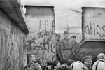 East German soldiers appear behind a piece of the wall torn down by the crowd next to the Brandenburg Gate on November 11, 1989
