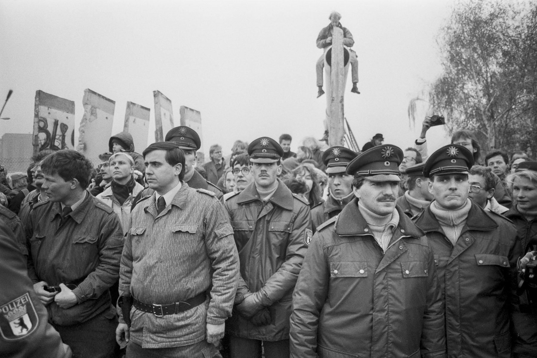 East German soldiers and West German policemen by a removed section of the Berlin Wall on Potzdamer Platz on November 11, 1989