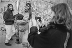 West Berliner women pose for photos in front of a gap in the Berlin Wall on November 11, 1989