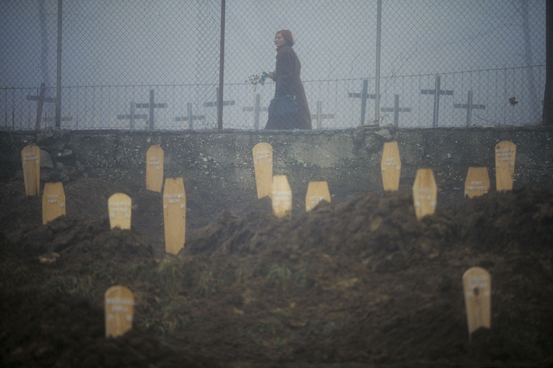An inhabitant of Sarajevo walking between the Christian and Muslim cemeteries dug in sports grounds near the Olympic stadium in December 1992