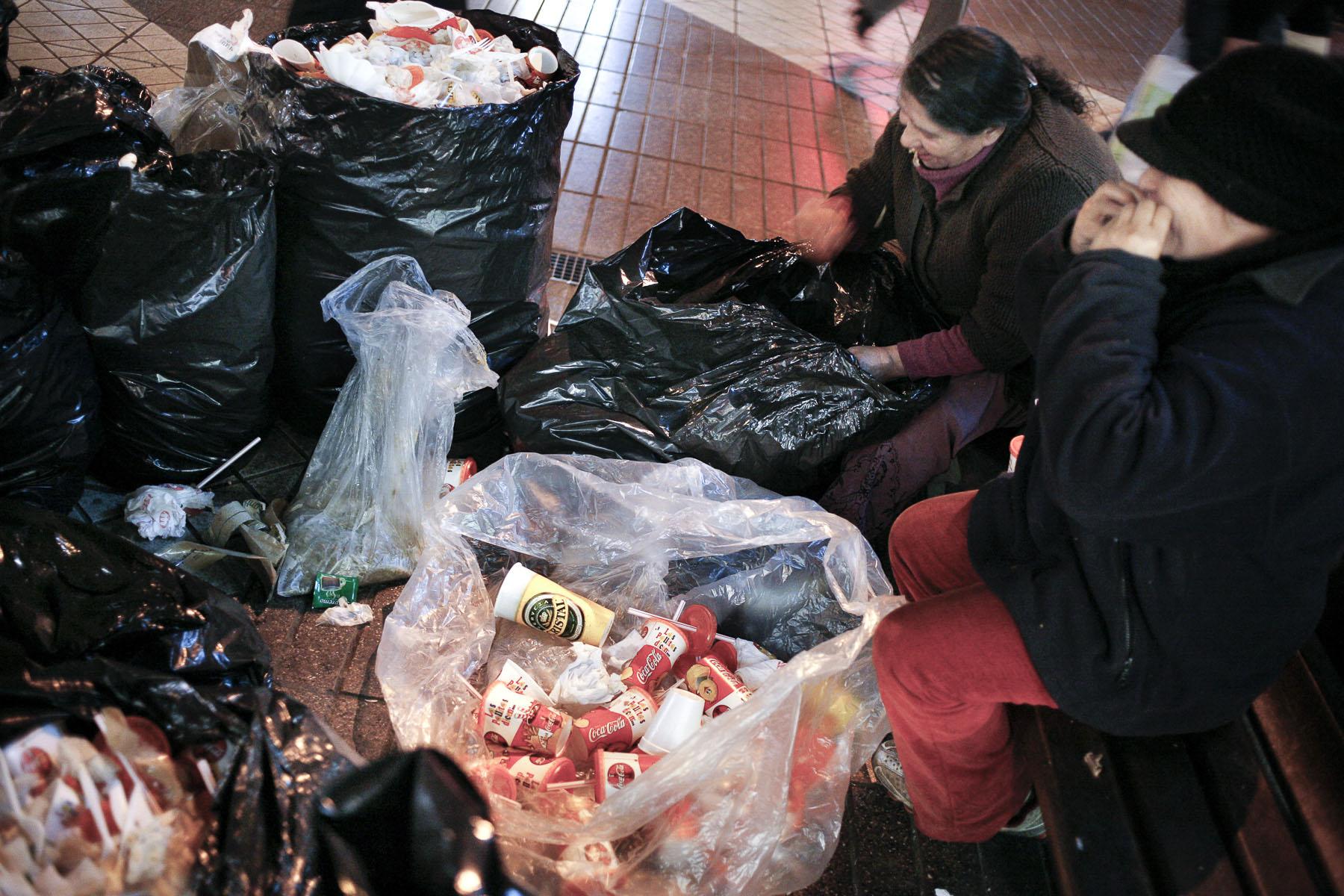 Near the Plaza de Armas, two women eat from a fast-food  rubbish bin in September 2007