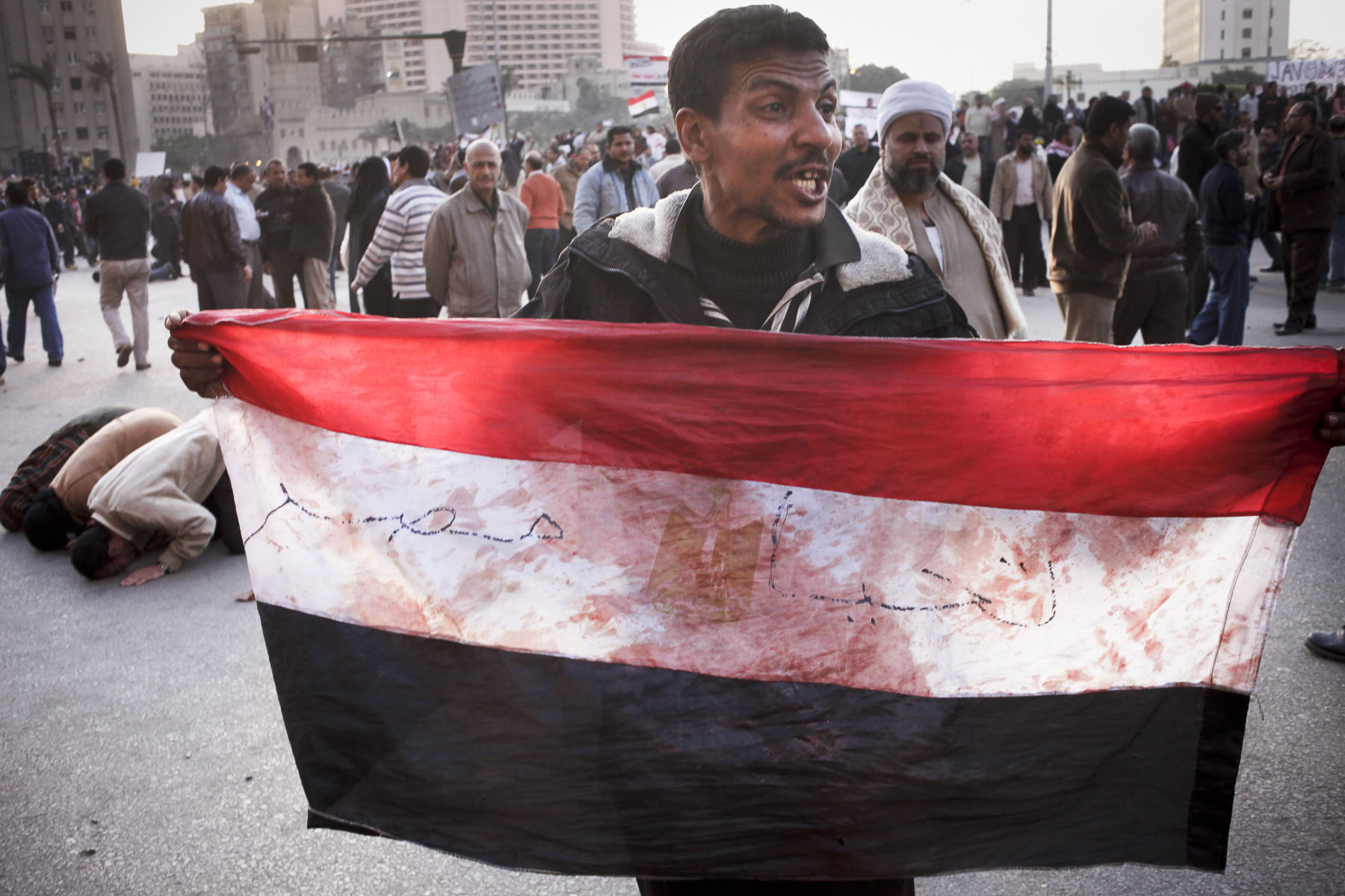 An anti-government demonstrator shows a bloody Egyptian flag during a clash with President Mubarak's supporters on Tahrir Square on Wednesday February 2 2011
