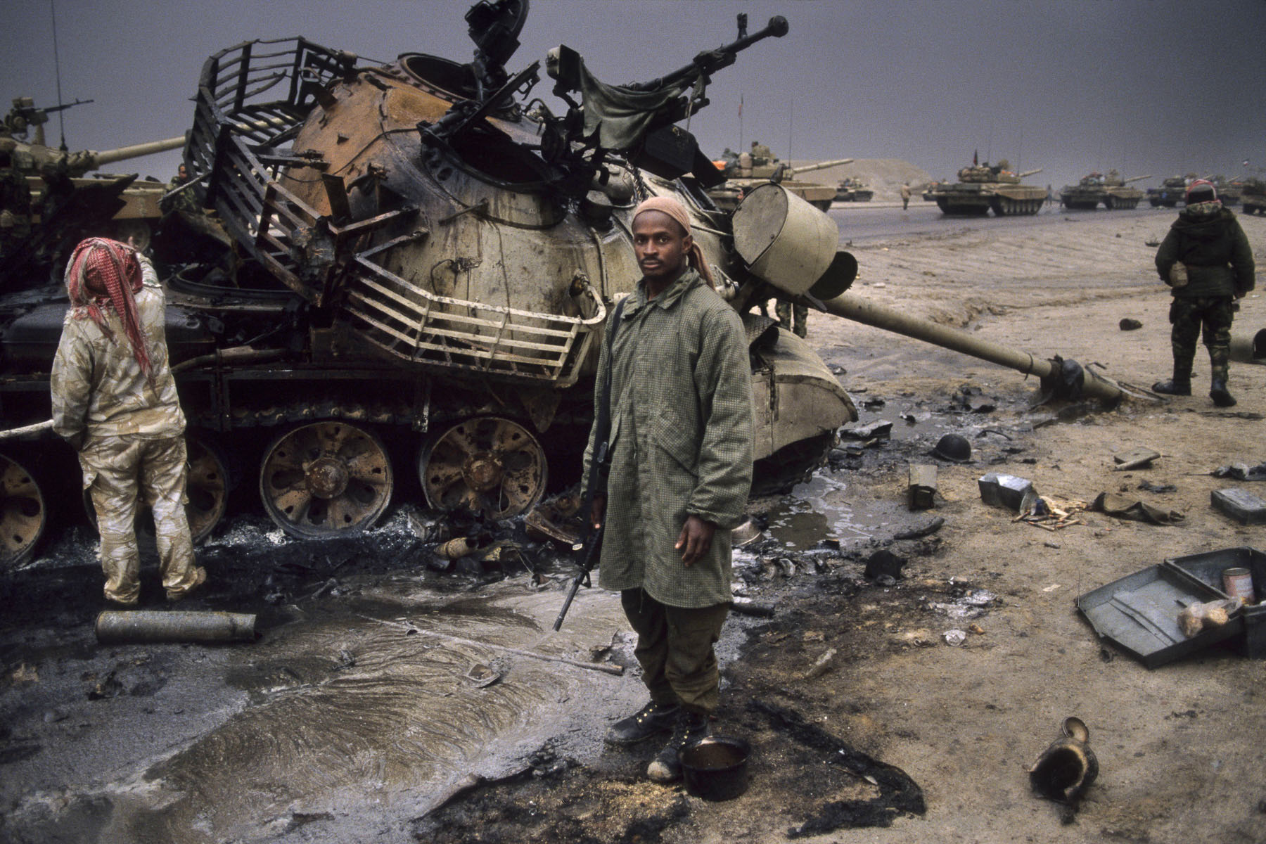 U.S. soldier stands in front of a destroyed Iraqi tank in February 1991