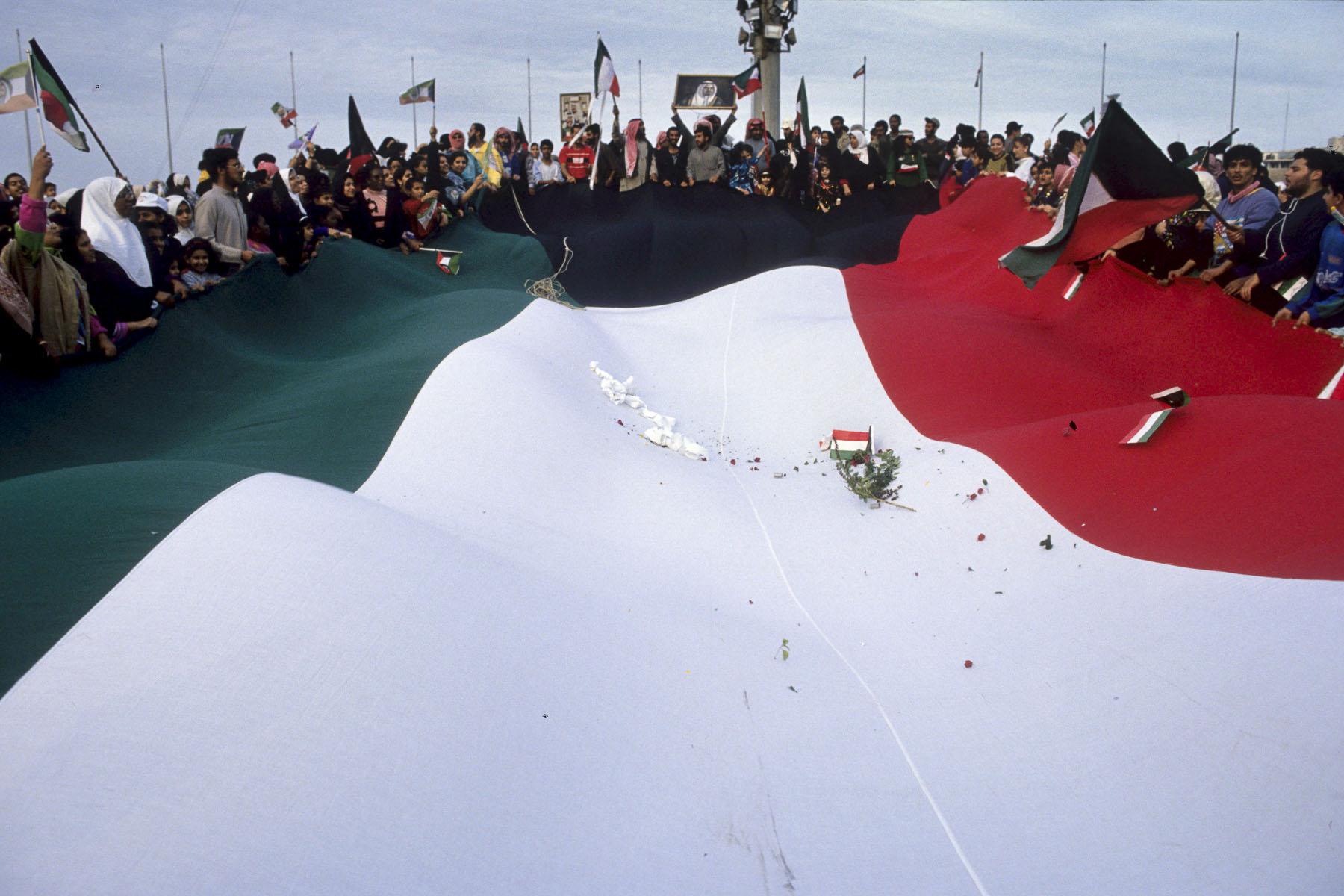 Kuwaiti celebrate the arrival of the coalition troops around a huge flag of Kuwait in February 1991