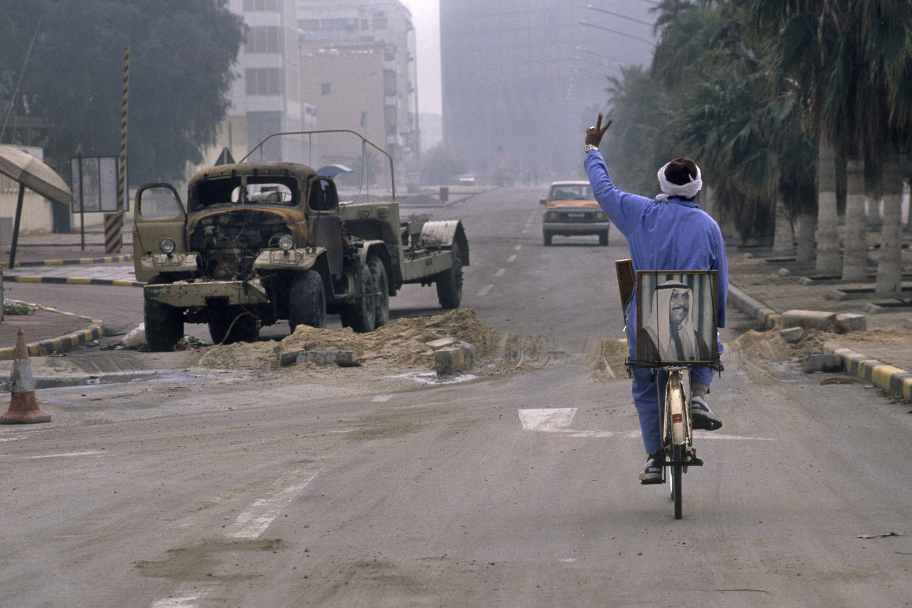 A man on his bicycle with the portrait of Sheik of Kuwait Saad Al-Abdullah Al-Salem Al-Sabah in February 1991