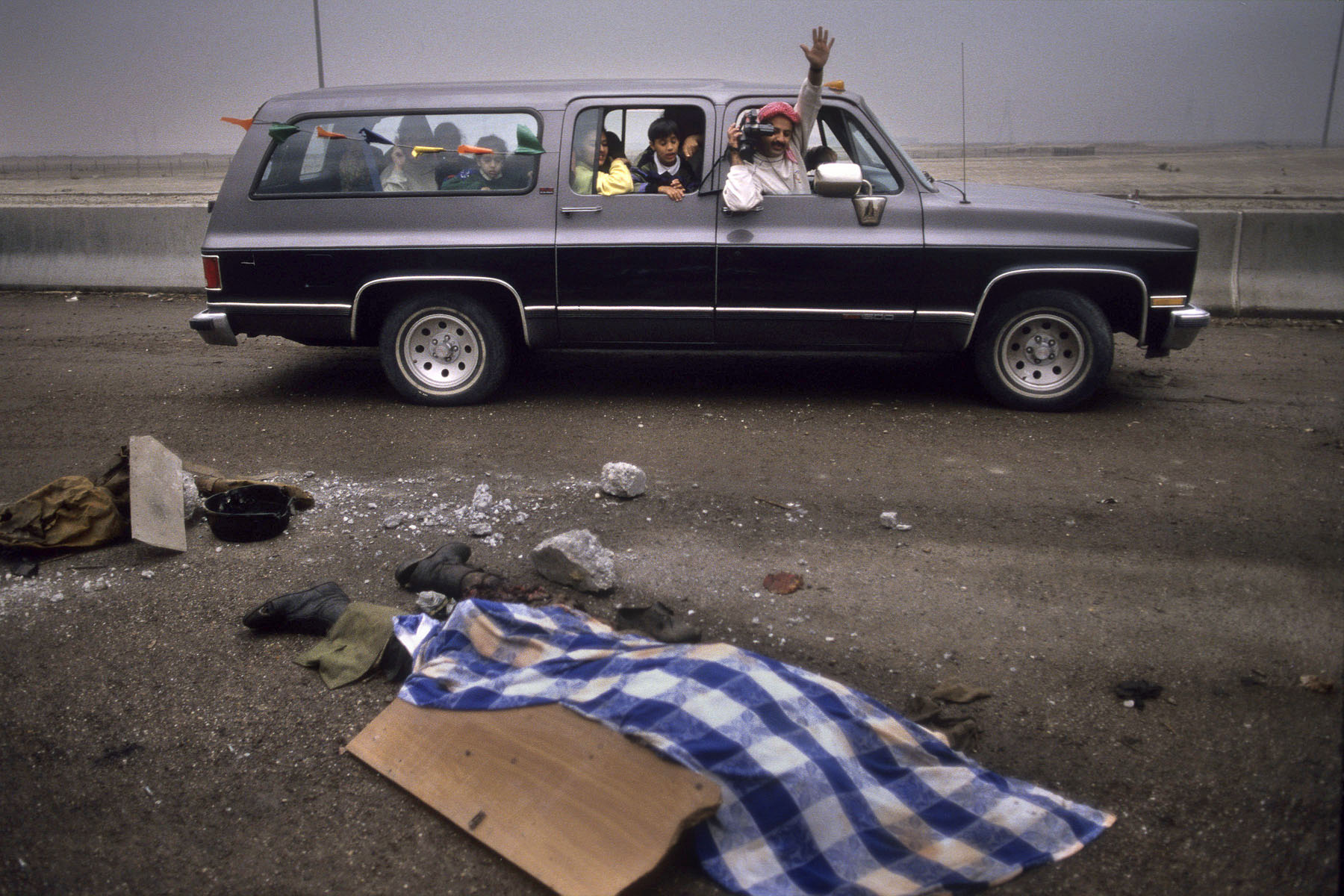 On the road to Basra, a Kuwaiti family drives past an Iraqi soldier's corpse in February 1991