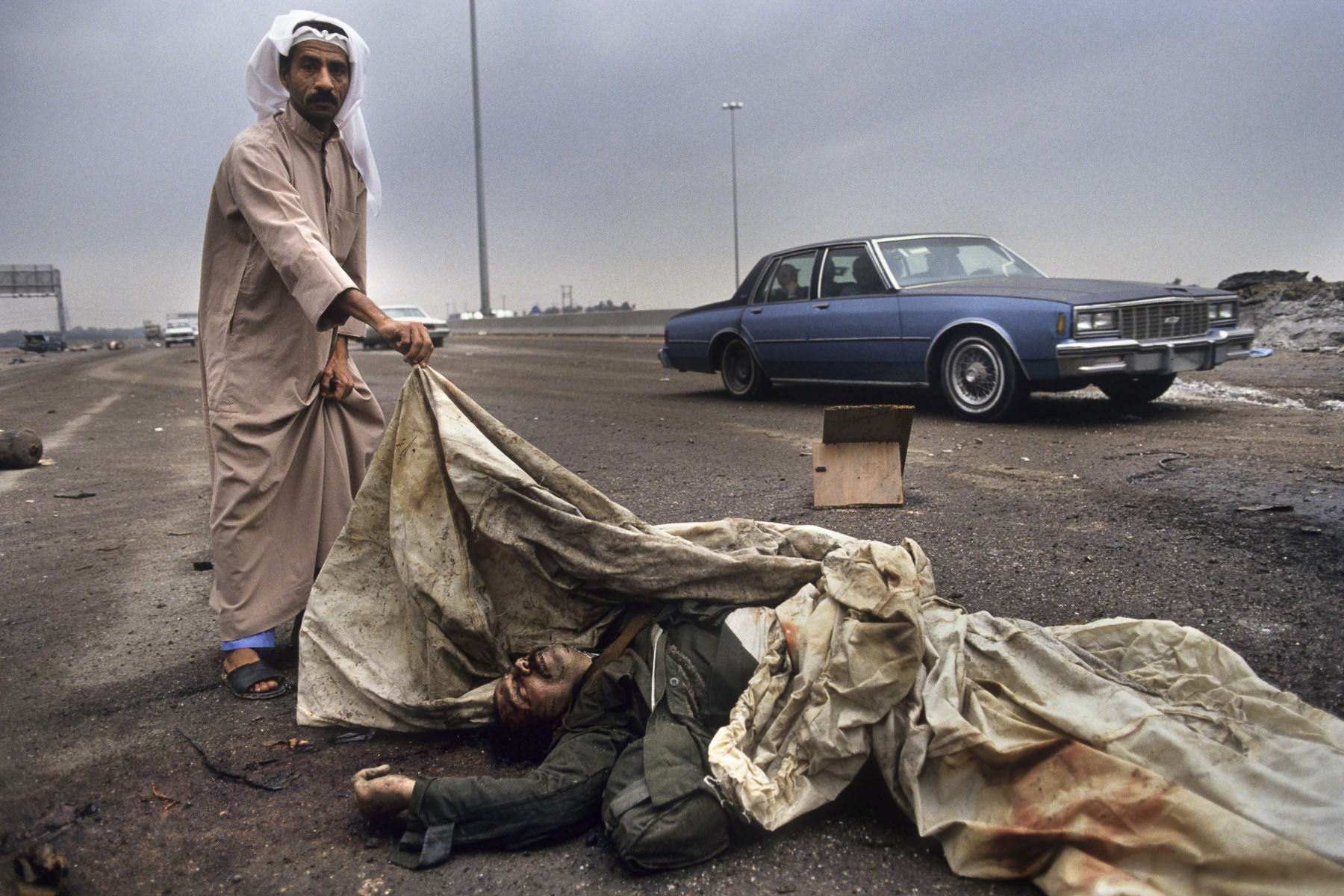 A Kuwaiti man showing an Iraqi soldier's corpse on the road to Basra in February 1991