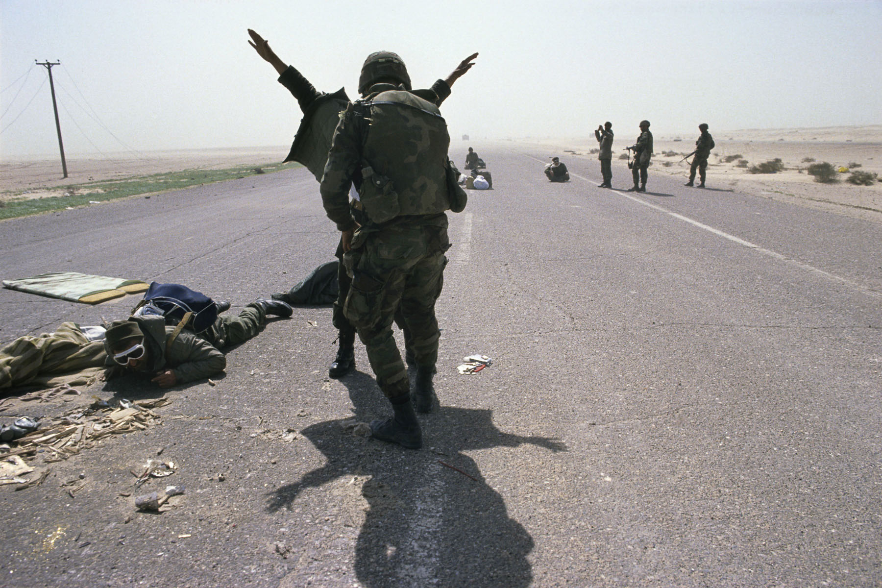 U.S. soldiers arrest Iraqi soldiers on the road to Basra in February 1991