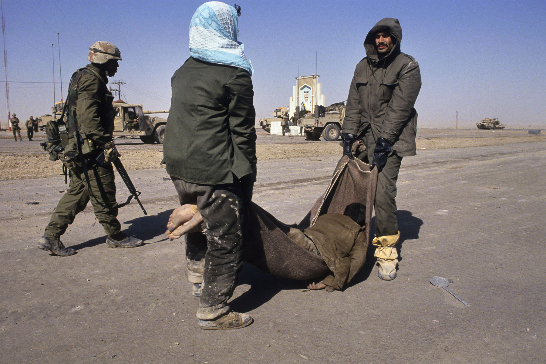 Two Iraqi prisoners carry their friend's body on the road to Basra in February 1991
